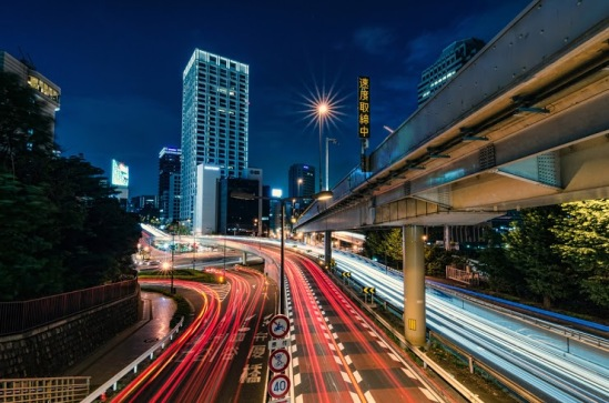 Cars zoom by on a July evening in the heart of Tokyo